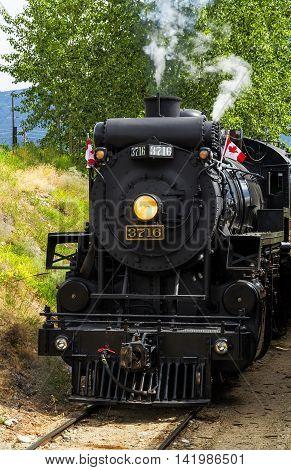 Photo of running steam train on sunny summer day