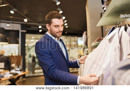 sale, shopping, fashion, style and people concept - elegant young man in suit choosing clothes in mall or clothing store