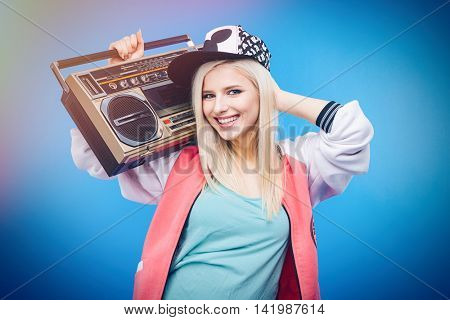 Smiling female teenager holding retro boom box on blue background