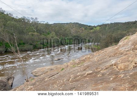 Elevated view overlooking the scenic Bell Rapids of the Swan River with large natural rock formations under a cloudy sky in the Swan Valley in Western Australia.