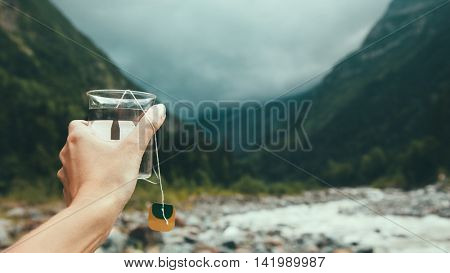 Closeup photo of mug with tea bag in traveler's hand over out of focus mountains view, tourizm in cold season