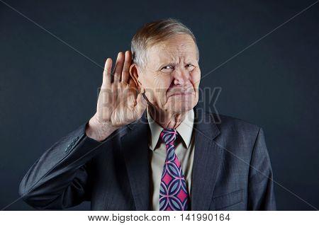 Businessman hold hand near ear over black background. Deaf businessman trying to listen