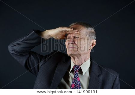 Businessman portrait, man looking far away isolated on black background with empty copy space