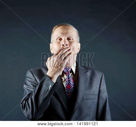 Elderly businessman hand near mouth,  yawning, isolated on black background