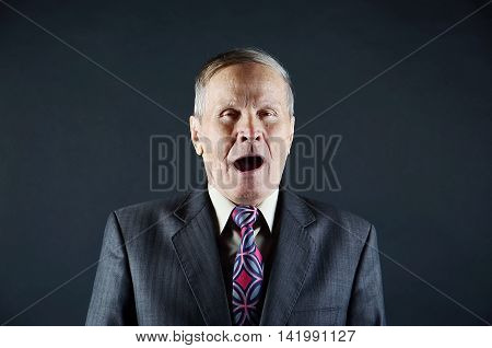 senior business man  yawning, isolated on black background