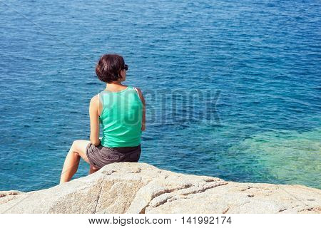 Young caucasian woman sitting on the rock and looking at blue sea. Woman seen from behind plenty of copy space on the right.