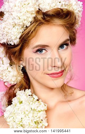 Beautiful young woman with natural make-up and wreath of white flowers on her head smiling at camera. Pink background. Summer, spring inspiration. Beauty, fashion, cosmetics.