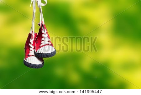 Sport baby shoes hanging on the green grass background