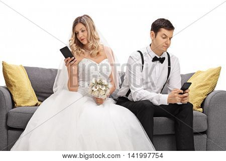Young married couple seated on a sofa looking at their phones and ignoring each other isolated on white background