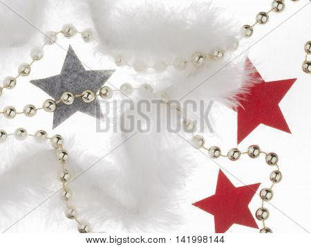Beautiful Christmas and New Year decoration - red gray stars out of soft felt the big star of the white fluff and gold beads on a white background isolated