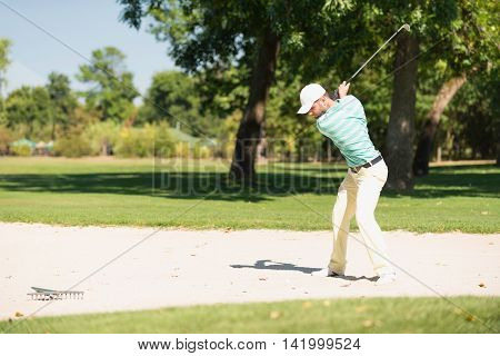 Golfer playing from sand trap, toned image