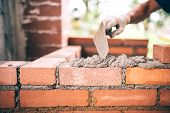 Industrial Construction Bricklayer Worker Building Walls With Bricks, Mortar And Putty Knife. poster