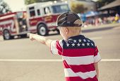 Постер, плакат: Boy watching a firetruck drive by during a parade procession during an Independence Day parade in a