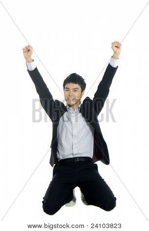 A young business man joyously throws his hands up in the air.