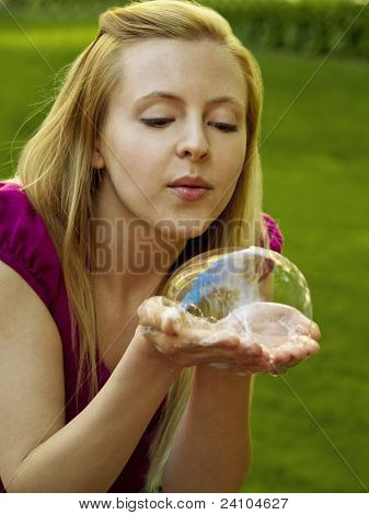 Happy girl blowing soap bubbles