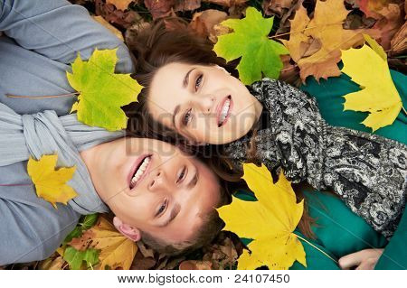 Smiling young people couple lying down on autumn maple leaves at fall outdoors