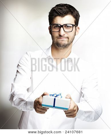 portrait of a handsome young man giving a gift indoor