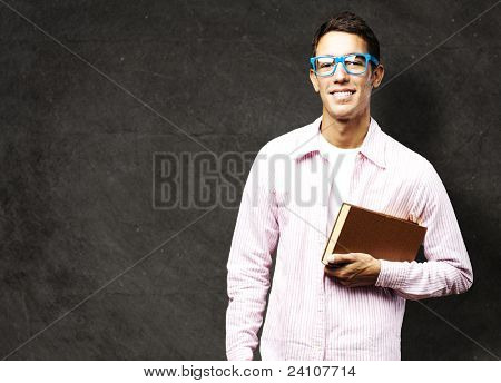 portrait of young student holding a book against a grunge background