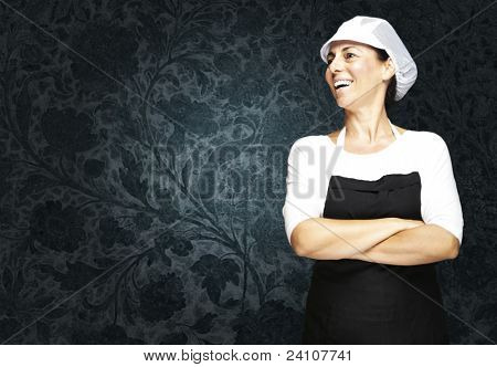 portrait of middle aged woman with apron and mesh top hat against a vintage background