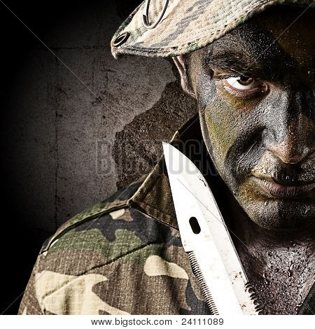 portrait of young soldier trying to suicide against a grunge wall