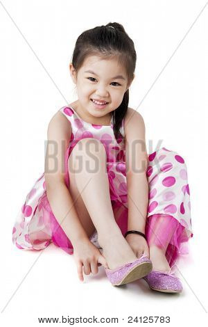 Little girl putting on her shoe