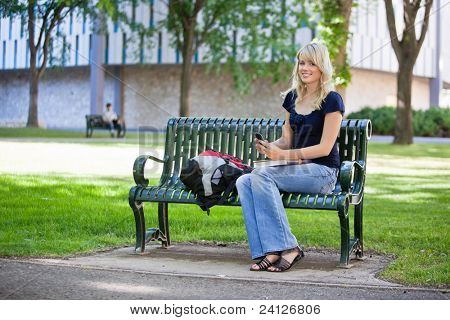 Young female student holding cell phone while sitting in college campus