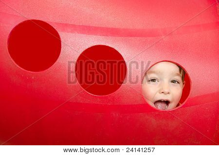 Young boy or kid playing in red tunnel outdoors on playground