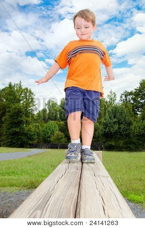 Young boy or kid balancing on beam obstacle on exercise trail outdoors at park