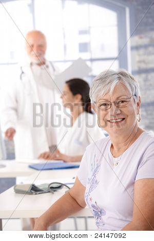 Elderly lady sitting at doctor's room, waiting for health control, smiling.