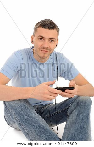 Casual Young Man With Cell Phone And Headphones. Isolated