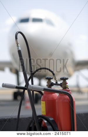 Fire Extinguisher And A White Airliner In The Background