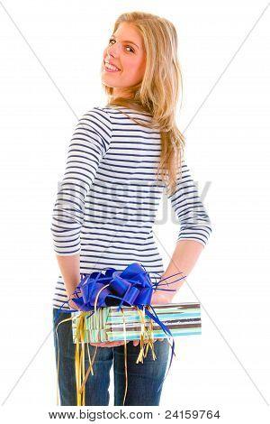 Smiling Teen Girl Hiding Present Behind Back