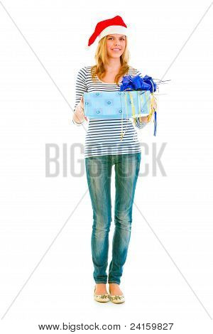 Full Length Portrait Of Lovely Teen Girl In Santa Hat Presenting Gift