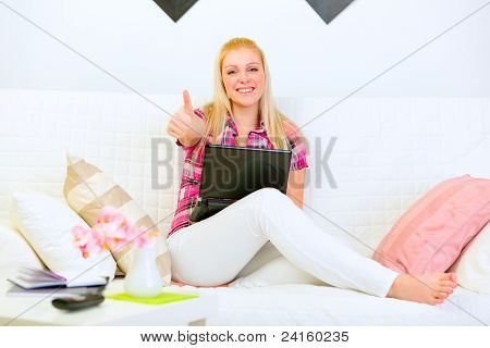 Smiling Beautiful Woman Sitting On Sofa With Laptop And Showing Thumbs Up Gesture