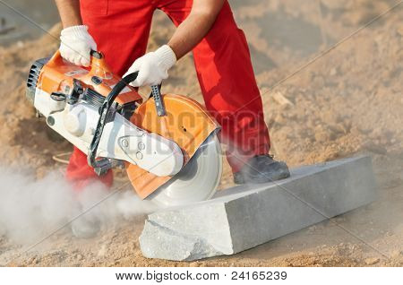 construction worker at curb stone cutting work by cut-off saw with diamond wheel