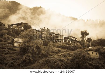 Houses in mountains covered by clouds and rain