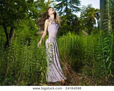 Portrait of a beautiful young woman dancing in the forest