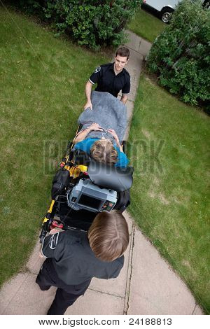Overhead view of emergency medical team pushing senior woman on stretcher.  Shallow DOF sharp focus on patient