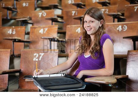 Portrait of young woman in lecture hall writing in binder