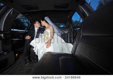 Loving newlywed bride and bridegroom in car