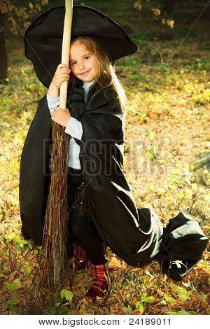 Tiro de una pequeña niña en traje de halloween posando con escoba y calabaza al aire libre.