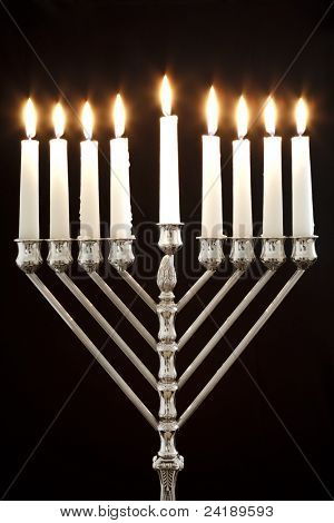 Silver Hanukkah candles all candle lite on the traditional Hanukkah menorah on a black background