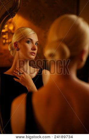 Beautiful woman reflected in vintage mirror