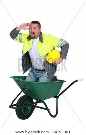 Construction worker in a wheelbarrow