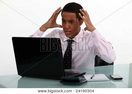 Frustrated young businessman being driven crazy by his computer
