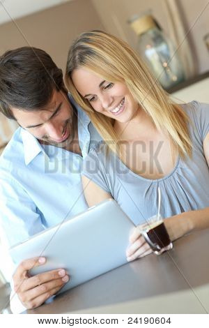 Young couple at home using electronic tablet