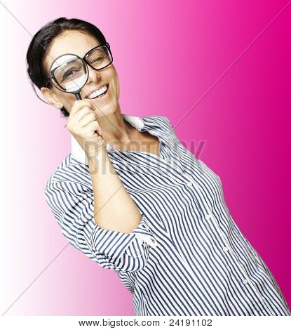 portrait of woman with looking through a magnifying glass against a pink background
