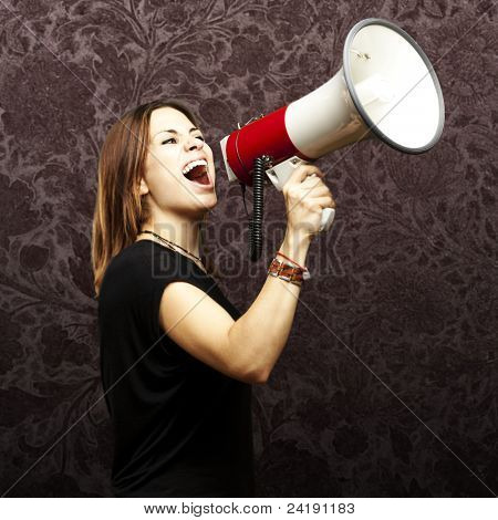 portrait of young woman shouting with megaphone against a grunge background