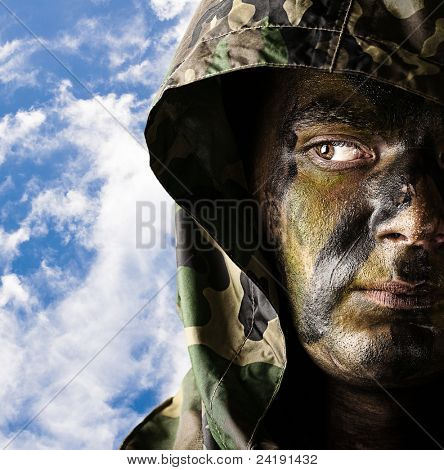 portrait of young soldier face wearing hood against a cloudy sky background