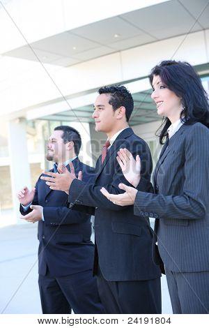 Attractive diverse man and woman business team clapping at office